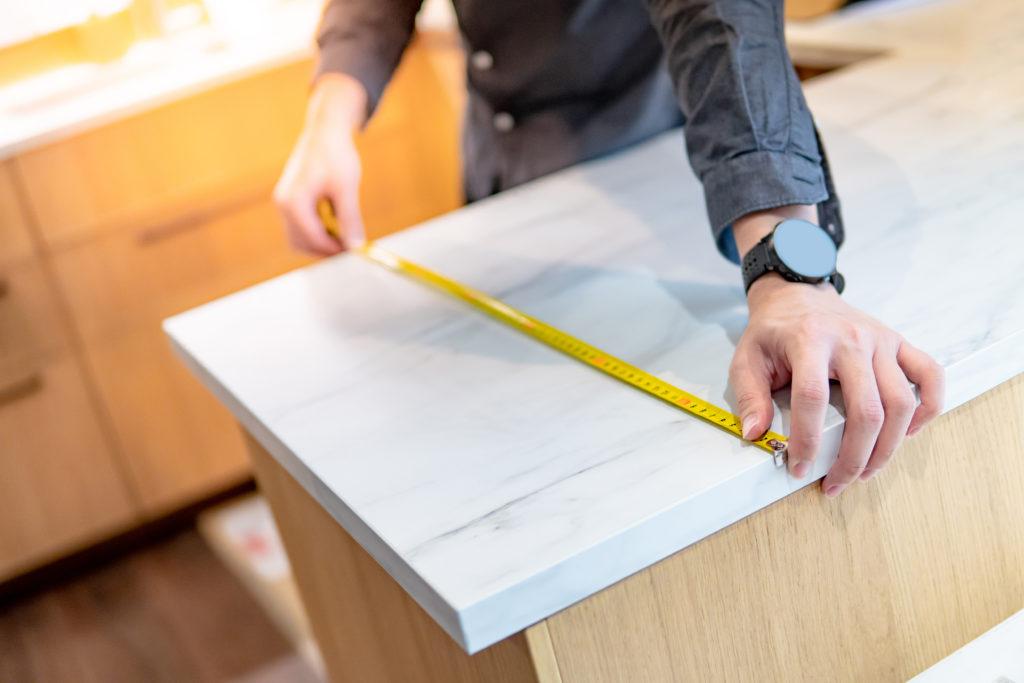 homme qui mesure le plan de travail de sa cuisine avec un mètre