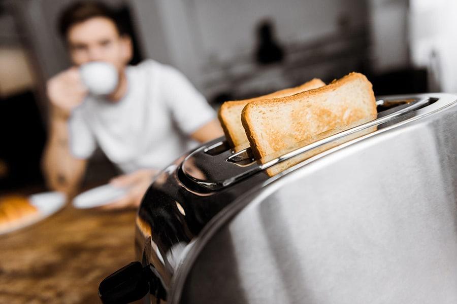 Homme en train de se faire des toasts pour le petit déjeuner